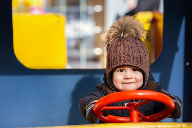 Очаровательный маленький мальчик играет на игрушечной машине снаружи