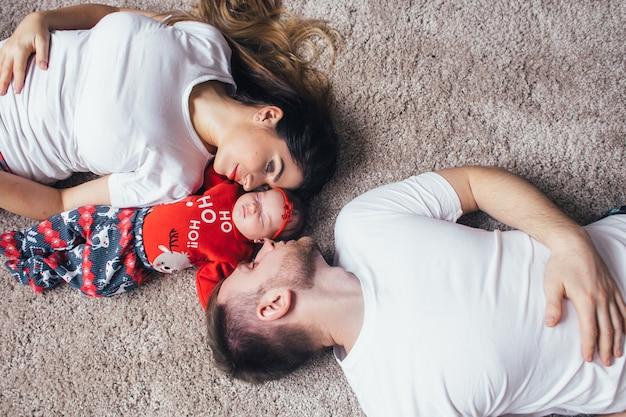 美しい両親が娘を床に着せている