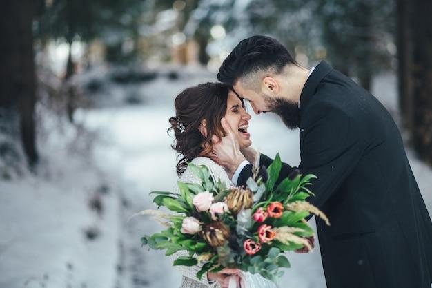 Бородатый мужчина и его прекрасная невеста позируют на снегу в волшебном зимнем лесу