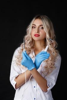 女性の医者は、顔の皮膚のためのガジェットと立っている