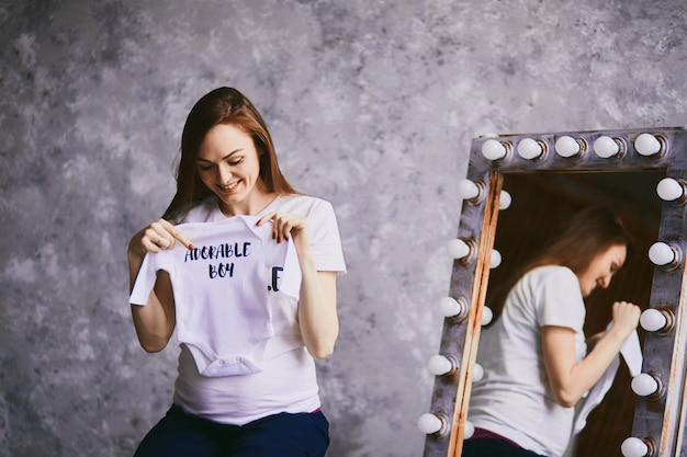 Будущая мать держит рубашку для ребенка