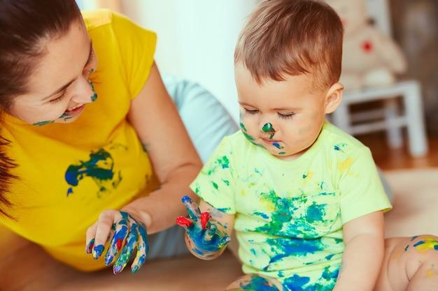 Мать с сыном рисует большую бумагу своими руками