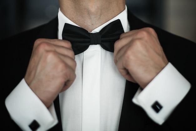 男は白いシャツに黒い蝶ネクタイを怒らせる