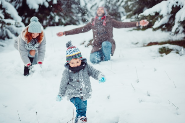 小さな子供が雪に沿って走っている