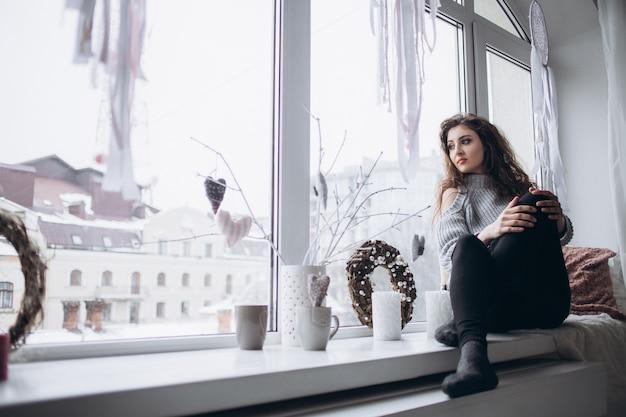 窓の上に座っているスタイリッシュな女の子