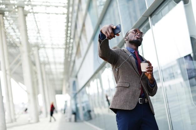 音楽に耳を傾けながらアフリカ系アメリカ人のビジネスマンが踊ります