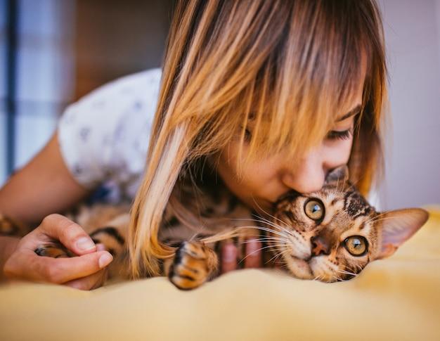 女性とベンガルの猫はベッドの上に横たわっています
