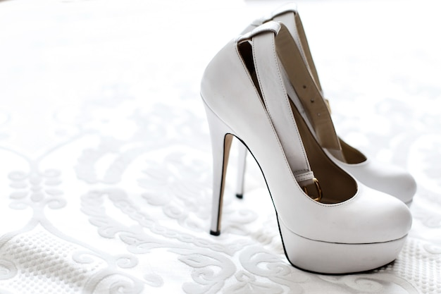 上品な白いプラットフォームの靴は、白い刺繍布に立つ