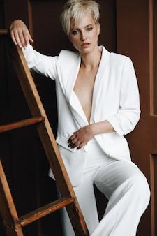 Блондинка с короткими светлыми волосами позирует в белом костюме по лестнице