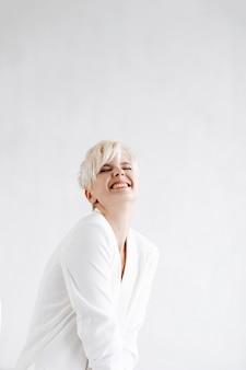 Женщина в белом костюме выглядит смешно позирует перед белой стеной