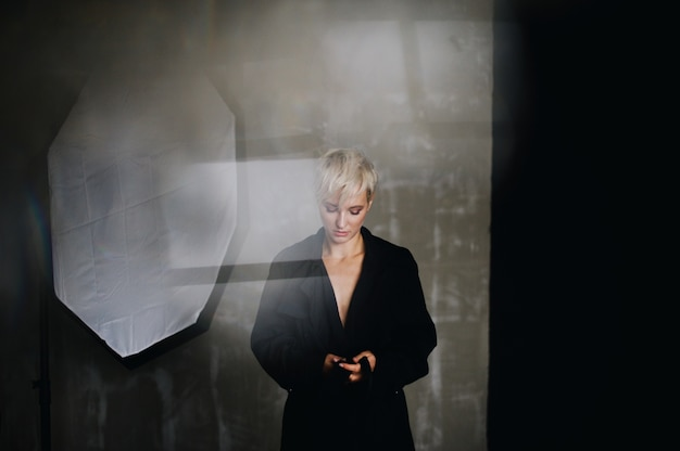 Потрясающая модель с короткими белыми волосами позирует в черном пальто перед мягкой коробкой