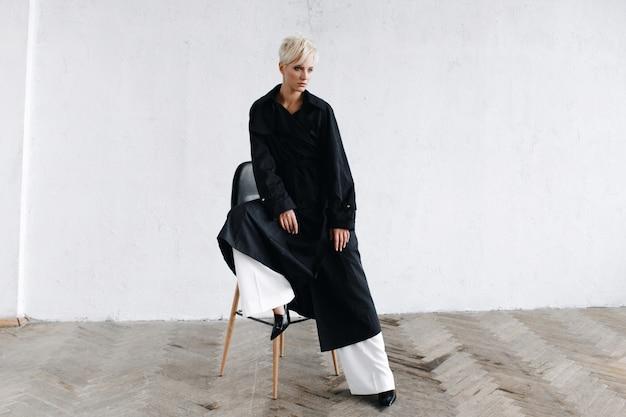 Модель в черном пальто сидит на стуле перед тем, как белая стена задумается
