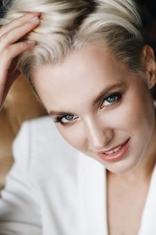Портрет белой блондинки с короткими волосами и глубокими голубыми глазами