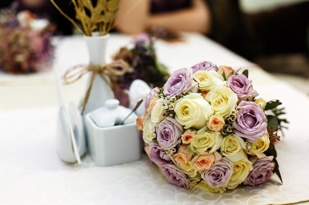 ベージュと紫のバラで出来たゴージャスな結婚式の花束