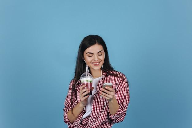 ミルクシェイクで笑顔の女の子は彼女のスマートフォンをチェックします