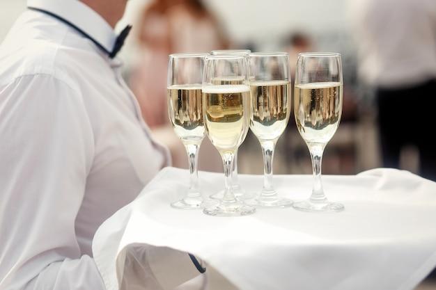 白のウェイターはシャンパンのフルートでトレイを運ぶ