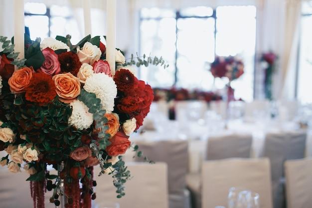 バラとピンの花束は、レストランの夕食のテーブルに立つ
