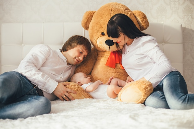 Мать, отец и сын лежат возле медведя на кровати