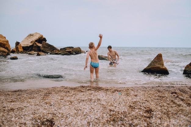 Двое детей играют на пляже в море между камнями