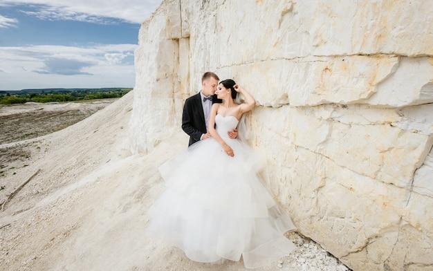 花嫁は、花婿の山の近くに屋外で歩く結婚式の日に新郎。