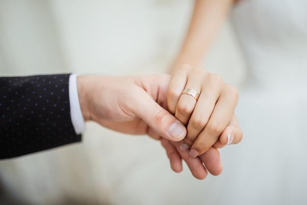 結婚の瞬間。結婚指輪を持つ新婚カップルの手