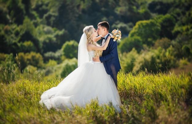自然の中でキスするウェディングドレスの恋人、新郎、花嫁の若いカップル。