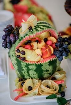 Арбуз с персиками и виноградом на белой тарелке