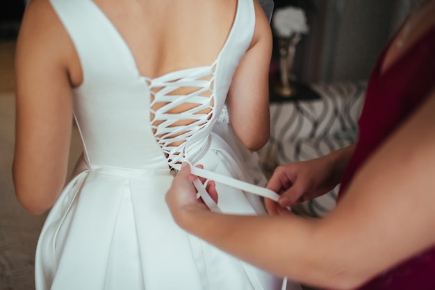 結婚式の準備。花嫁が彼女のウェディングドレスを着るのを助ける。