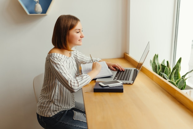 若いビジネスは、ネットブックのキーボードで入力し、メモ帳のメモで作業します。