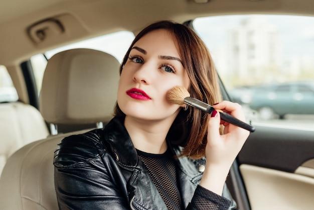 Молодая девушка ретушируя ее макияж, когда остановился в движении