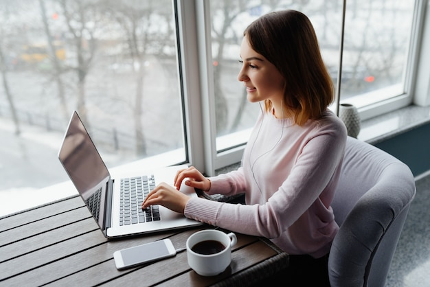 若いビジネスは、ネットブックのキーボードで入力し、音楽を聞く。