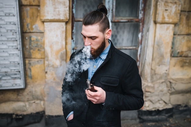 屋外で気化器を吹き飛ばすモデルベーパー。安全な喫煙。ヤングベーパー。