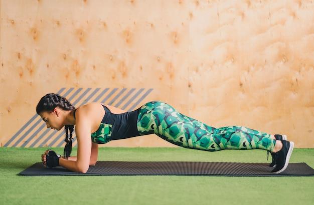 健康的な若い女性は、ジムで板張りのエクササイズをしています。