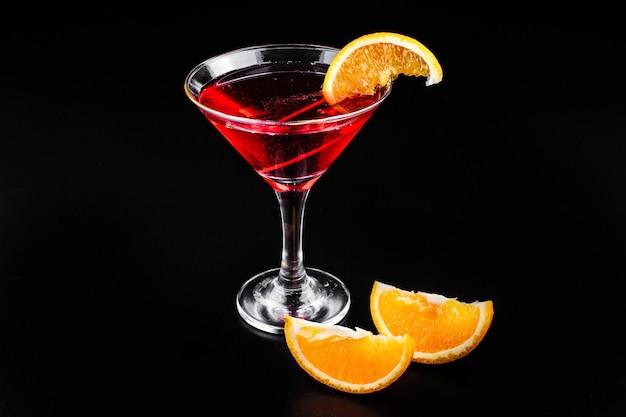 血のオレンジジンとトニックのカクテルは、ガラスのオレンジのスライスを添えて