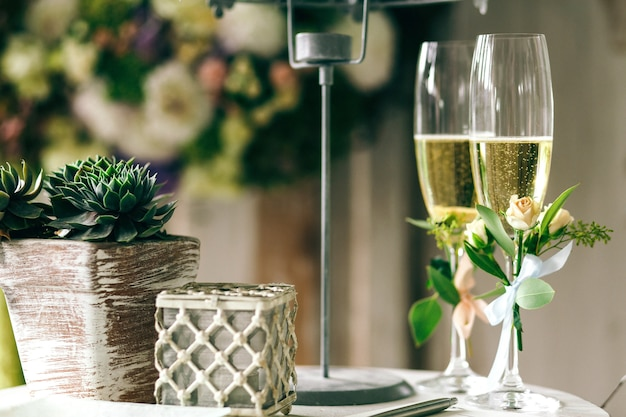 小さなバラで飾られたシャンパンフルートはテーブルに立つ