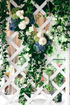 白と青の花の緑の花輪が壁にぶら下がっています