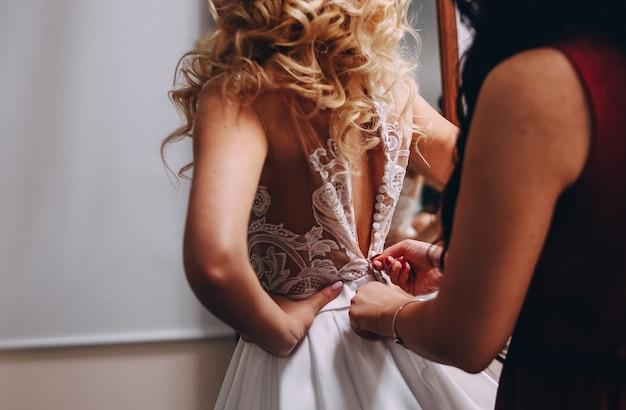 花嫁のブロンドのドレス美しいドレス女性は彼女のボタンを助ける背中に