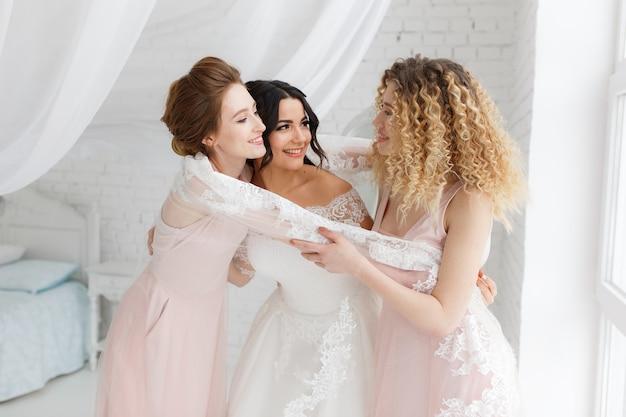朝の寝室で花嫁を抱擁しているブライドメイド。