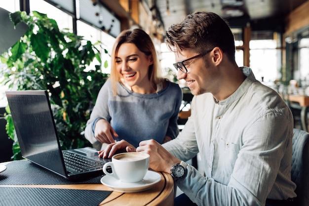 カラフルで笑うカフェに座って、ラップトップの画面を見ているカップル