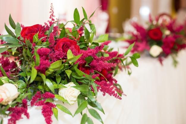 赤い花の花束は、レストランの白いテーブルに横たわっています