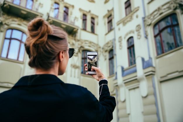 古い建物、建築、携帯電話を使用して写真を撮っている流行の女性