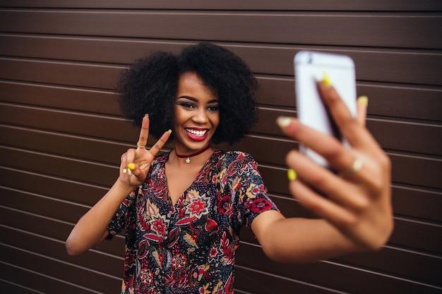 Молодая афро-американская девушка, показывая знак мира, принимая самоубийство на мобильный телефон.
