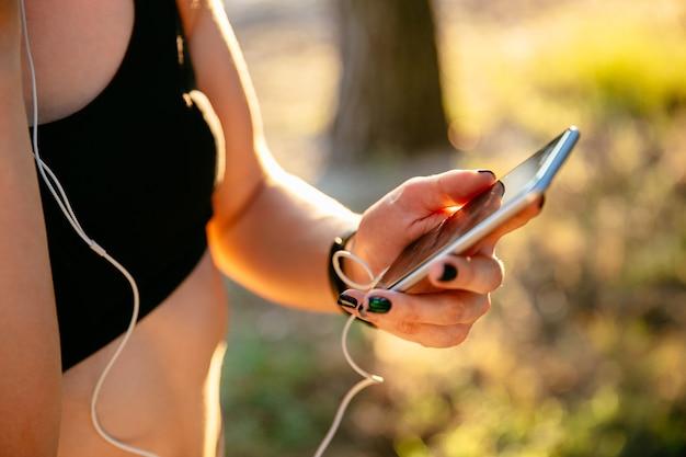Спортивная женщина в черной майке с помощью мобильного телефона во время прослушивания музыки