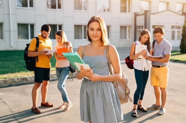 Красивая молодая девушка с красным бархатным рюкзаком с книгами