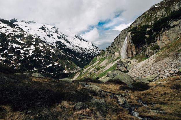 美しい夏山の中の滝のアルパインの風景