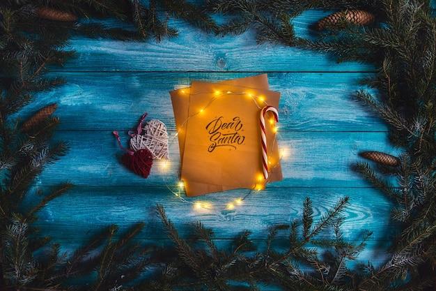 クリスマスの精神の青い木製のテーブルの上の親愛なるサンタへの手紙。