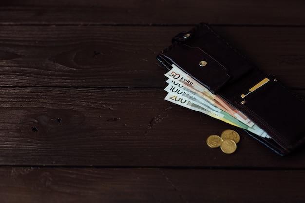 財布の中の現金。木製の背景に茶色の財布のユーロ現金