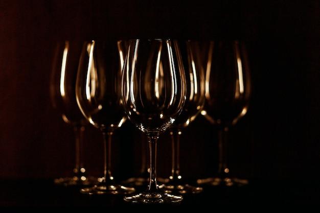 暖かい光で照らされたワイングラスは黒の背景に立つ