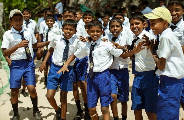 Школьники, одетые в форму, веселятся и играют на школьном дворе.