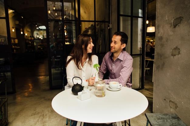 ロマンチックなデート。お互いを見て、笑っている彼らの日にカフェで恋に落ちたカップル